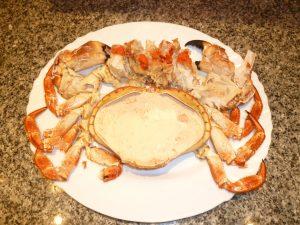 Buey de mar abierto y preparado para ser degustado. Relleno con una salsa hecha con su propia carne. Alrededor las pinzas y pasar partidas.