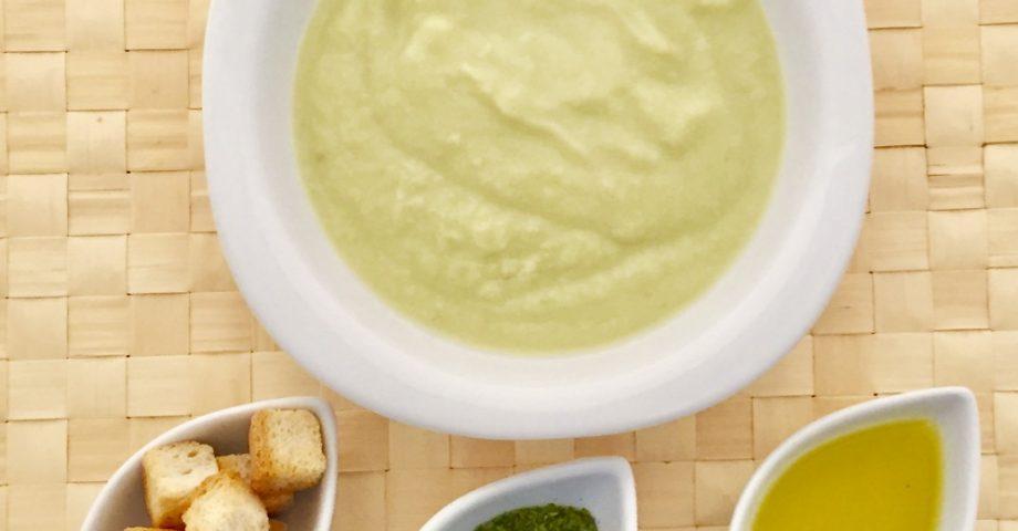 Vista cenital de un plato redondo y blanco con crema de espárragos verdes. Está sobre un mantel de fibra vegetal trenzada. Se observan tres recipientes ovalados que contiene cada uno picatostes, aceite de oliva virgen extra y perejil.