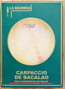 Envase de carpaccio de bacalao marca La Balinesa de 150 gramos. Se puede ver el producto a través de una ventana circular. Forma natural y saludable de bacalao.