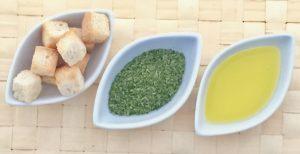 Detalle de una guarnición de picatostes tostados, perejil y aceite de oliva virgen extra