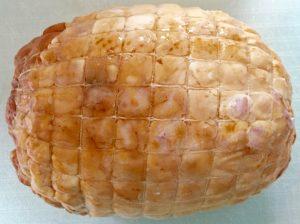 Aspecto que ofrece un redondo de pollo recién sacado de su envase. Se aprecia que está envuelto en una malla. Su color es dorado al estar asado.