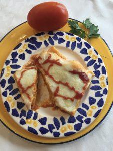 Lasaña boloñesa recién salida del horno presentada en un plato en el que aparece un tomate entero y una rama de perejil.