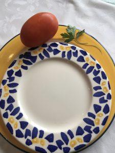 Plato con un tomate natural y una rama de perejil