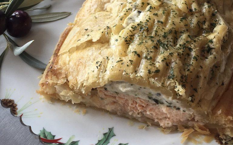 Presentación de hojaldre de salmón con crema de espinacas en un plato con motivos navideños