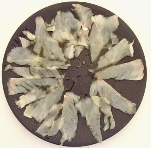 Disposición del carpaccio de bacalao en el plato para continuar añadiendo ingredientes. Forma natural y saludable de bacalao.