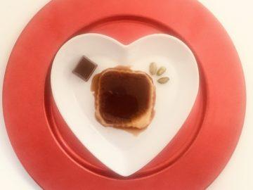 Tocino de cielo con chocolate y pistachos. Tiene forma cuadrada y está presentado sobre un plato en forma de corazón blanco y un sobre plato rojo. Se observa un bombón de chocolate y unos pistachos tostados pelados.