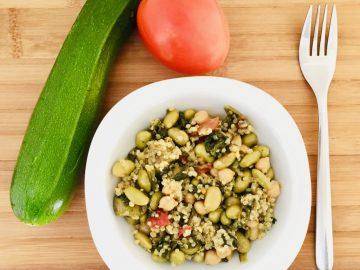 Quinoa con verduritas salteadas. Sobre una tabla color madera aparece un bol con el salteado. Alrededor hay un calabacín, un tomate y un tenedor.
