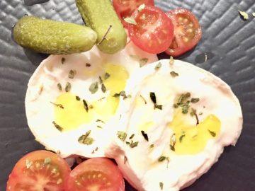 Tapa de mozzarella con cherry y pepinillos. Sobre un plato negro con aceite y orégano.