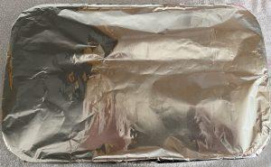 Recipiente para horno cubierto con papel aluminio.